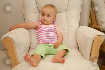 Sitting on a chair stock photo, Little caucasian baby girl sitting on a chair by Mariusz Jurgielewicz