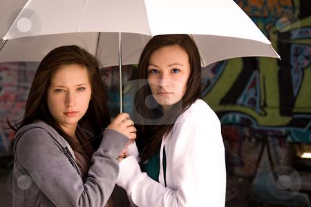 Two Teenage Girls Under a White Umbrella stock photo, Two Teenage Girls Under an Umbrella as a Protection by Mehmet Dilsiz