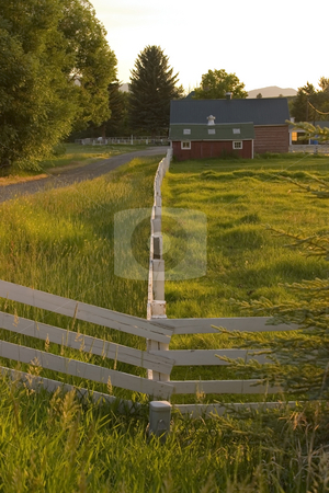 Countryside Fence Leading to A Ranch stock photo, Wooden Fence by the Countryside Ranch by Mehmet Dilsiz