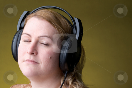 Woman listing to music stock photo, Women listing to music with her eye close by Yann Poirier