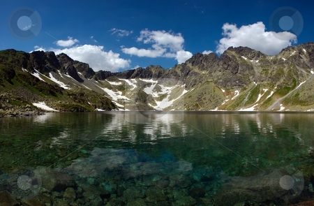 Mountain lake with pure water stock photo, Mountain lake with clear pure water and under surface view in sunny summer day with some clouds by Juraj Kovacik
