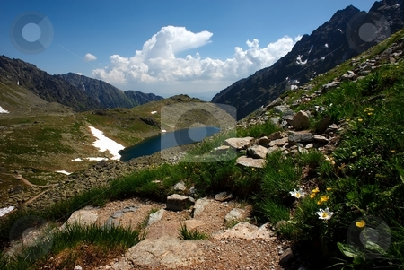 Walking path in mountains with lake and flowers stock photo, Walking path in mountains with lake and flowers in summer day by Juraj Kovacik