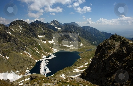 Tourists on a peak stock photo, Tourists on a peak in summer day with mountain lake in valley by Juraj Kovacik