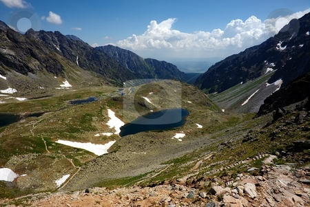 Meandering walking path in mountains stock photo, Meandering walking path in mountains with lake and sunny cloudy sky by Juraj Kovacik