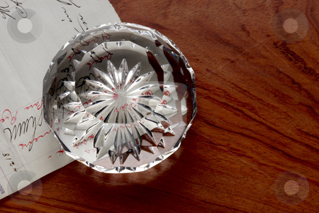 Desktop still life stock photo, Cut crystal paperweight sits on handwritten note and wooden desk by James Barber