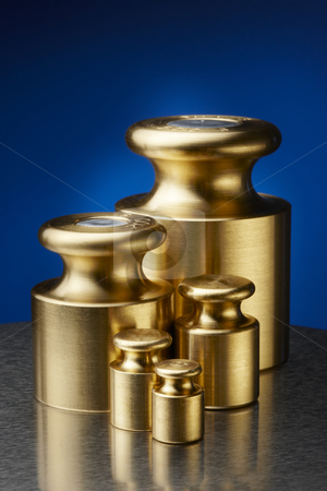 Weights stock photo, Five different brass weights shot on stainless scale by James Barber
