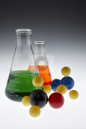 Colorful chemicals and molecules stock photo, Colorful chemicals in beekers and molecule models on surface lit from below by James Barber