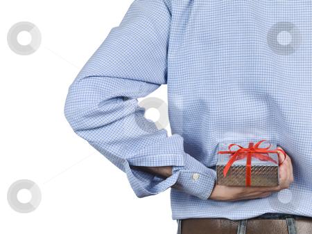 Surprise stock photo, Young man hiding a gift box behind his back. by Ignacio Gonzalez Prado