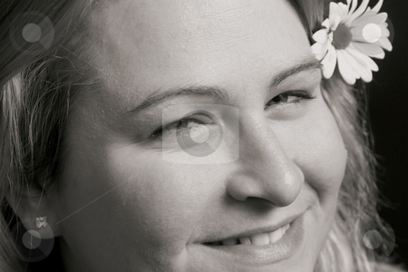 Women smiling stock photo, Close up of a women smiling with a flower in her hair by Yann Poirier