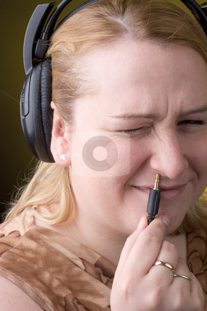 Women wrong plugin stock photo, Women trying to plugin headset in her nose with any success by Yann Poirier