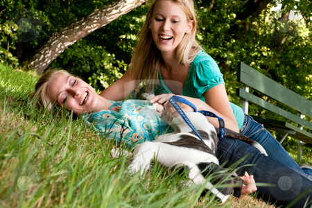 Playfull doggie stock photo, Two blond girls and a american bulldog in the park by Frenk and Danielle Kaufmann