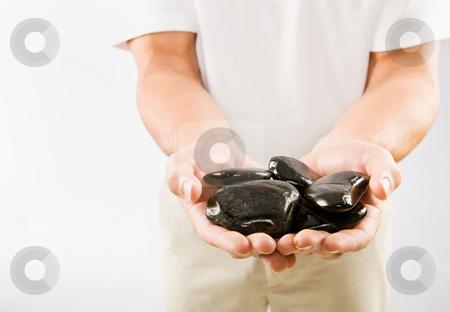 Massage therapist holding warm stones stock photo, Massage therapist holding warm stones by Jonathan Ross