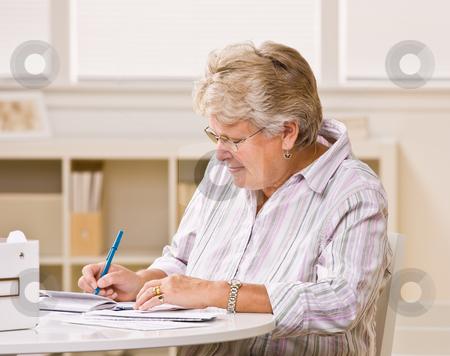 Senior woman writing checks stock photo, Senior woman writing checks by Jonathan Ross