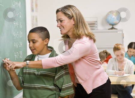 Teacher helping student at blackboard stock photo, Teacher helping student at blackboard by Jonathan Ross