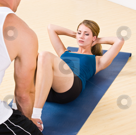 Trainer helping woman do sit ups stock photo, Trainer helping woman do sit ups by Jonathan Ross