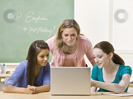 Teacher helping students on laptop stock photo, Teacher helping students on laptop by Jonathan Ross