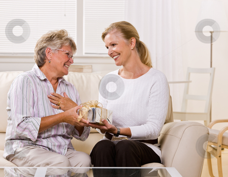 Daughter giving mother gift stock photo, Daughter giving mother gift by Jonathan Ross