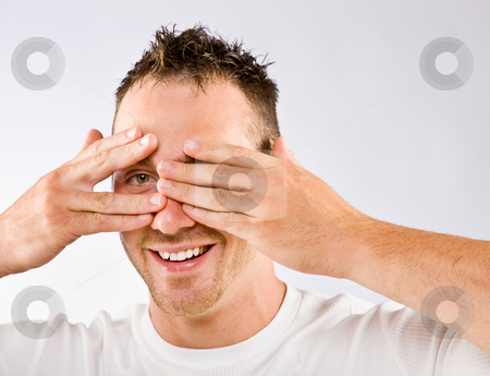 Man peering from behind hands stock photo, Man peering from behind hands by Jonathan Ross