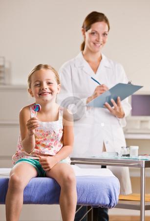 Girl eating lollipop in doctor?s office stock photo, Girl eating lollipop in doctor?s office by Jonathan Ross