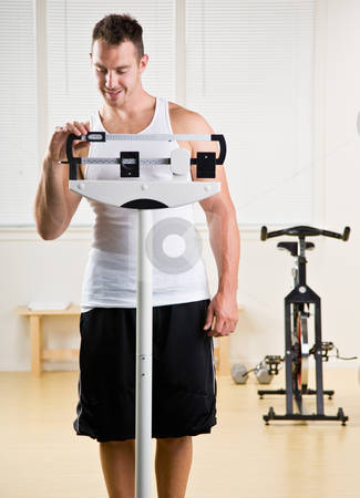 Man weighing himself in health club stock photo, Man weighing himself in health club by Jonathan Ross