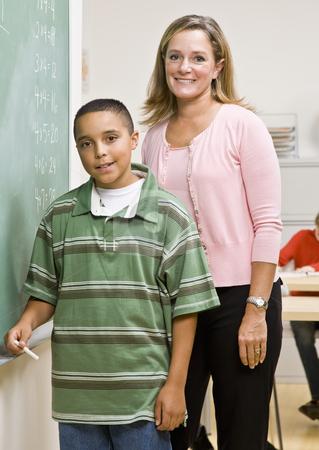 Teacher helping student at blackboard stock photo, Teacher helping student at blackboard by Jonathan Ross