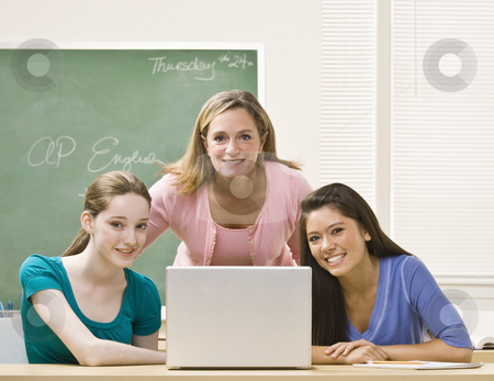 Teacher helping students on laptop stock photo, Teacher helping students on laptop by Jonathan Ross