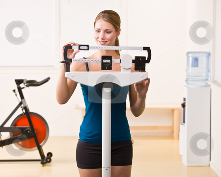 Woman weighing herself on scales in health club stock photo, Woman weighing herself on scales in health club by Jonathan Ross