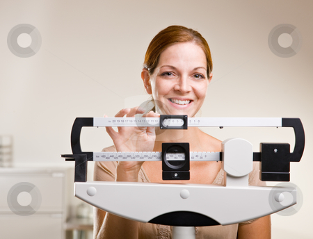 Woman weighing herself in doctor?s office stock photo, Woman weighing herself in doctor?s office by Jonathan Ross