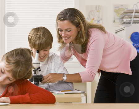 Teacher helping student with microscope stock photo, Teacher helping student with microscope by Jonathan Ross