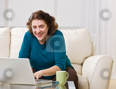 Senior woman using laptop in livingroom stock photo, Senior woman using laptop in livingroom by Jonathan Ross