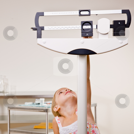 Girl weighing herself in doctor?s office stock photo, Girl weighing herself in doctor?s office by Jonathan Ross