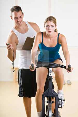 Trainer timing woman on stationary bicycle stock photo, Trainer timing woman on stationary bicycle by Jonathan Ross