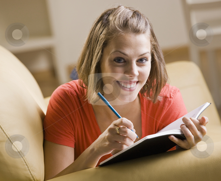 Teenage girl writing in book stock photo, Teenage girl writing in book by Jonathan Ross