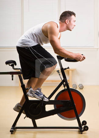 Man riding stationary bicycle in health club stock photo, Man riding stationary bicycle in health club by Jonathan Ross
