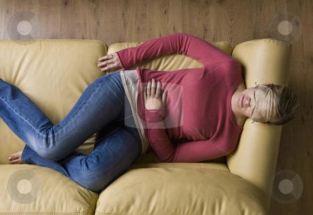 Woman laying on sofa wearing sleep mask stock photo, Woman laying on sofa wearing sleep mask by Jonathan Ross