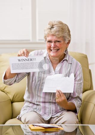 Senior woman holding ?winner? notification stock photo, Senior woman holding ?winner? notification by Jonathan Ross