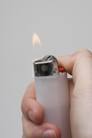 Hand holding a lighter stock photo, Women hand holding a white lighter with flame on white background by Yann Poirier