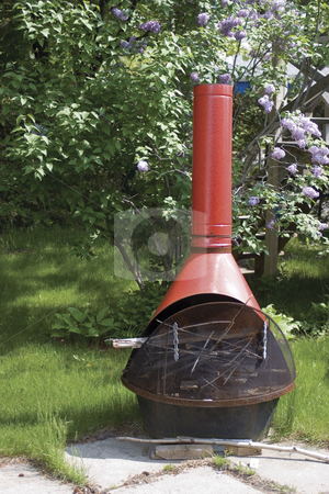 Outdoor fire place stock photo, Metal outdoor fire place with lilac background by Yann Poirier