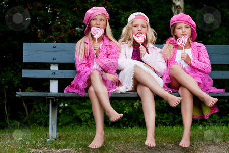 3 Sisters eating a lollipop stock photo, Happy children having pink clothes and a lollipop by Frenk and Danielle Kaufmann
