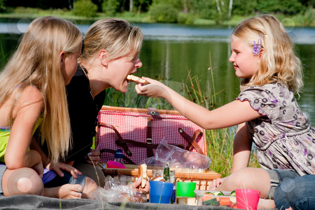 Young girl feeds her mother stock photo, Happy children having fun in the park by Frenk and Danielle Kaufmann