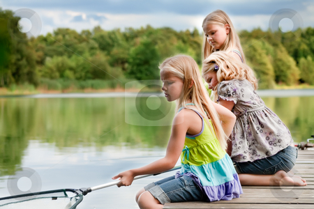 The girls are fishing stock photo, Happy children having fun in the park by Frenk and Danielle Kaufmann