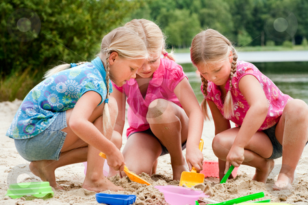 The girls digging in the sand stock photo, Happy children having fun in the park by Frenk and Danielle Kaufmann