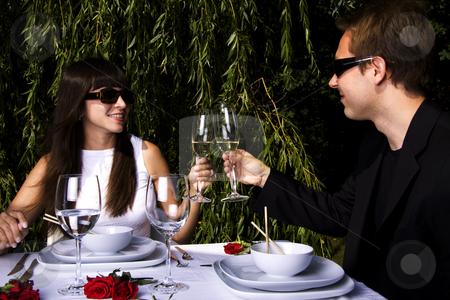 Lunch in the garden stock photo, Couple having a romantic lunch in the garden enjoying wine by Daniel Kafer