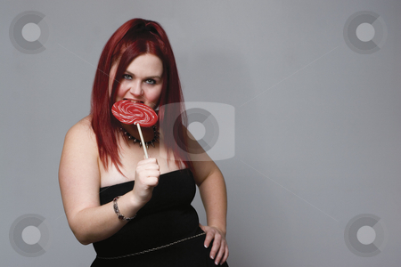 Goth rock red hair chick - lollipop stock photo, Red hair female model in goth look bitting on big red lollipop by Yann Poirier