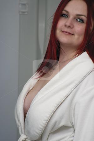 Red hair model with open bathrobe stock photo, Red hair woman model in open white bathrobe standing in bathroom by Yann Poirier