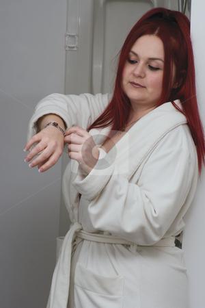 Red hair model in bathroom stock photo, Red hair woman model in white bathrobe standing in bathroom playing with bracelet by Yann Poirier