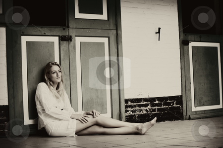Sitting against the stable door thinking my thoughts stock photo, Blond beauty in white sitting at the floor against the stable doors. by Frenk and Danielle Kaufmann