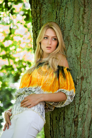 Blond beauty in yellow blouse leaning against a tree stock photo, Beautifull blond posing against a tree by Frenk and Danielle Kaufmann