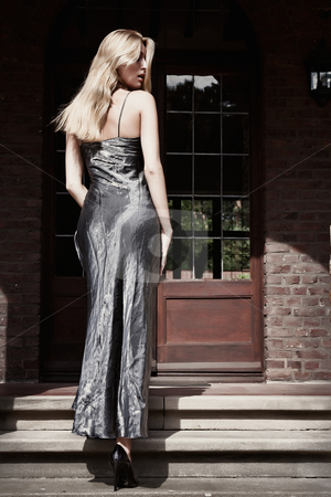 Blond princess walking up the stairs looking over her shoulder stock photo, Blond young woman dressed like a princess entering her castle by Frenk and Danielle Kaufmann