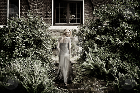 Blond beauty in a castle garden dressed for gala stock photo, Beautifull blond in gala dress walking away from viewer, climbing up some stairs in a castle garden by Frenk and Danielle Kaufmann
